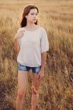 Маленькая девочка с длинным коричневым пребыванием волос на луге стоковая фотография rf