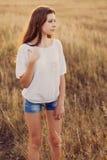 Маленькая девочка с длинным коричневым пребыванием волос на луге стоковое изображение rf