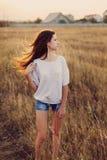 Маленькая девочка с длинным коричневым пребыванием волос на луге стоковое фото