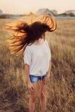 Маленькая девочка с длинным коричневым пребыванием волос на луге стоковые изображения rf