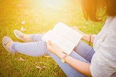 Маленькая девочка с книгой в зеленом саде Стоковые Изображения RF