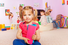 Маленькая девочка с книгой в классе Стоковая Фотография