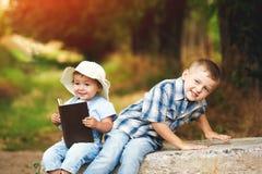 Маленькая девочка с книгой и братом в парке на заходе солнца Стоковое фото RF