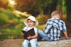 Маленькая девочка с книгой и братом в парке на заходе солнца Стоковое Фото