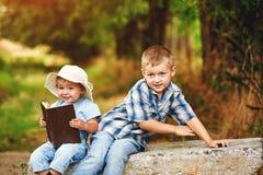 Маленькая девочка с книгой и братом в парке на заходе солнца Стоковые Фото