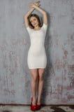 Маленькая девочка с красивой диаграммой в ультрамодном белом платье в кож-плотной одетых мини-юбке и красных высоких пятках и пла Стоковые Изображения