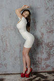 Маленькая девочка с красивой диаграммой в ультрамодном белом платье в кож-плотной одетых мини-юбке и красных высоких пятках и пла Стоковая Фотография