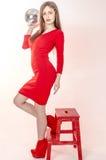 Маленькая девочка с красивой диаграммой в ультрамодном красном платье в кож-плотной мини-юбке и красных высоких пятках и платформ Стоковая Фотография