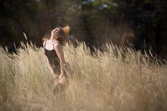 Маленькая девочка с красными волосами в поле стоковое изображение