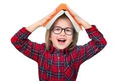Маленькая девочка с кучей книг на голове изолировано Стоковые Фотографии RF