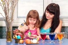 Маленькая девочка с мамой красит пасхальные яйца перед праздником Стоковые Фото