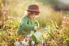 Маленькая девочка с моча чонсервной банкой в саде Стоковая Фотография RF