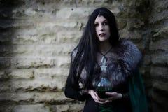 Маленькая девочка с накидкой меха и склянка с зельем Выглядеть как костюм хеллоуина Стоковое Изображение RF