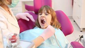 Маленькая девочка с открытым ртом во время сверля обработки на дантисте акции видеоматериалы