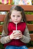 Маленькая девочка с питьем на скамейке в парке стоковая фотография