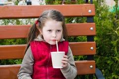 Маленькая девочка с питьем на скамейке в парке стоковое фото