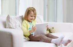 Маленькая девочка с планшетом дома Стоковые Фотографии RF