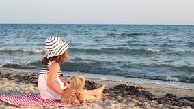 Маленькая девочка с плюшевым медвежонком на пляже видеоматериал