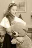 Маленькая девочка с плюшевым медвежонком около камина Стоковая Фотография