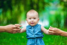 Маленькая девочка с справедливыми, короткими волосами в джинсы одевает без рукавов предпринимает меры первые шаги в парке в тепло Стоковые Изображения RF