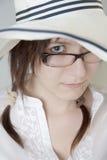 Маленькая девочка с стеклами смотря прищурясь вне из-под большой белой шляпы Стоковая Фотография