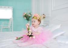 Маленькая девочка с тюльпанами сидит на кровати стоковое изображение rf