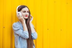 Маленькая девочка слушает к музыке в белых наушниках Стоковые Фото