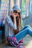 Маленькая девочка слушает к музыке в белых наушниках Стоковые Изображения RF
