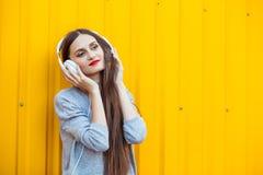Маленькая девочка слушает к музыке в белых наушниках Стоковые Изображения
