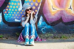 Маленькая девочка слушает к музыке в белых наушниках Стоковое Фото