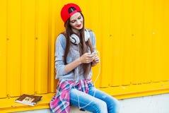 Маленькая девочка слушает к музыке в белых наушниках Стоковая Фотография