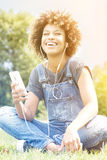 Маленькая девочка слушая к музыке в парке, ослабляя Стоковое Изображение