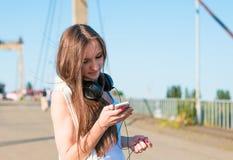 Маленькая девочка слушая к музыке в парке Студент снаружи с наушниками Стоковое Изображение RF