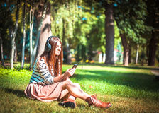 Маленькая девочка слушая к музыке в парке Стоковое Изображение