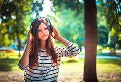 Маленькая девочка слушая к музыке в парке Стоковая Фотография