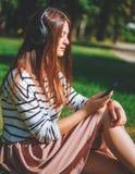 Маленькая девочка слушая к музыке в парке Стоковое Изображение RF