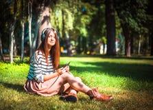 Маленькая девочка слушая к музыке в парке Стоковое Фото