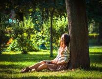 Маленькая девочка слушая к музыке в парке Стоковое фото RF