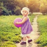 Маленькая девочка с фиолетовым воздушным шаром стоковая фотография