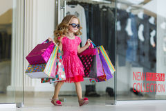Маленькая девочка с хозяйственными сумками идет к магазину стоковая фотография rf