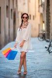 Маленькая девочка с хозяйственными сумками на узкой улице в Европе Портрет красивой счастливой женщины держа хозяйственные сумки Стоковая Фотография