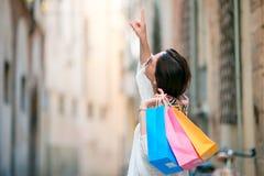 Маленькая девочка с хозяйственными сумками на узкой улице в Европе Портрет красивой счастливой женщины держа хозяйственные сумки Стоковые Фотографии RF