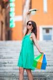 Маленькая девочка с хозяйственными сумками на узкой улице в Европе Портрет счастливой женщины держа хозяйственные сумки Стоковые Изображения RF