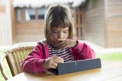 Маленькая девочка с цифровой таблеткой Стоковые Изображения