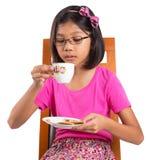 Маленькая девочка с чаем и печеньем i стоковое фото