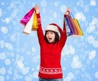 Маленькая девочка с шляпой santa рождества на ее голове, держа shopp стоковые фотографии rf