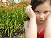 Маленькая девочка с яркими оранжевыми цветками Стоковое фото RF