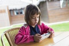 Маленькая девочка с smartphone Стоковые Фото