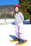 Маленькая девочка с snowshoes и шлемом Стоковое Фото