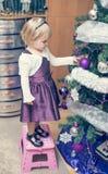 Маленькая девочка украшая дерево christmass Стоковая Фотография